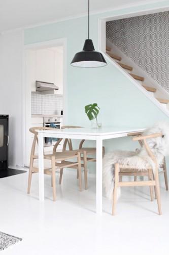 Un salon qui respire la fraîcheur et la luminosité avec sa peinture bleu pastel jouant sur la perspective grâce à l'escalier et au papier peint du mur en arrière plan