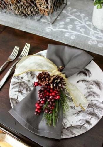 Complètement british cette déco de table de Noël joue avec les camaïeux de couleurs grise. Serviettes en toile de Jouy, branche de houx rouge et ruban jaune