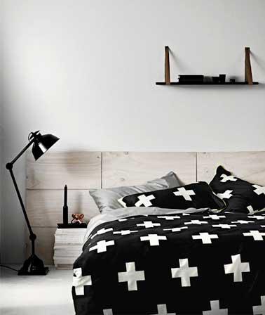 Déco graphique pour tête de lit réalisée en panneaux de bois clair blanchi. Mise en valeur par le ton noir du linge de lit et de la lampe articulé design.