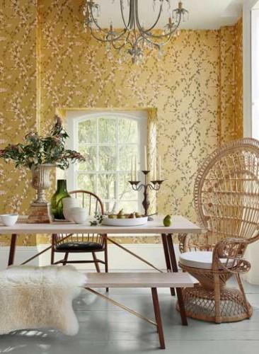 Ton délicat sur les murs et look scandinave dans la salle a manger. Déco avec chaise en rotin, table, banc clair et peau. Sakura papier peint Little Greene.