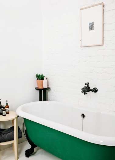 Une couleur de baignoire verte plante le décor de cette salle de bain. Une bonne idée à reprendre comme déco forte pour habiller une petite pièce monochrome