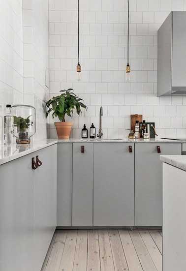 Blanc et gris, un duo de couleur intemporelle dans cette cuisine déco grise. Meuble gris, mur en carrelage métro blanc, sol en bois blanchi et détail cuir