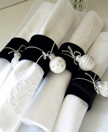 Un beau pliage de serviette à réaliser en déco de table de Noël sophistiquée. Avec des ronds de serviette et boules de Noël en couleurs chic blanc et argent