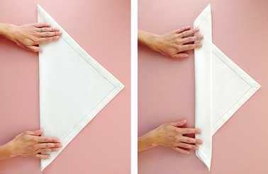 Avec une serviette dans un tissu épais, commencez le pliage de votre serviette de Noël. En deux étapes vous créez un triangle pour former la future chandelle