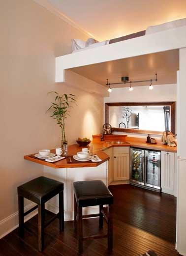 Ambiance rangée dans la petite cuisine du tiny house. Entièrement pensée sur mesure, meubles et plan de travail libèrent l'espace pour un gain de place maxi