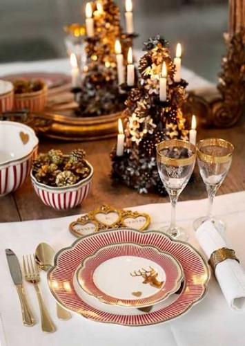 Passons Noël au château autour de cette table à la déco impériale rouge et or. Vaisselle en porcelaine blanche, couverts or, et déco en bois précieux.