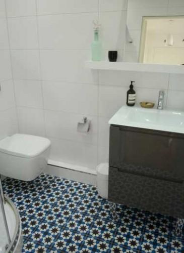 Carreaux de ciment mosaïque bleue pour une salle de bain zen. Murs en carrelage blanc et meuble sous vasque noir laquée se coordonnent parfaitement.