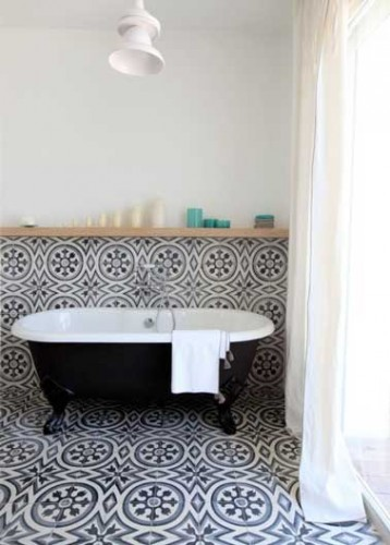 Duo noir et blanc intemporel dans cette salle de bain en carreaux de ciment sur le sol et les murs. Déco construite autour de la baignoire à pieds noir.