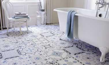 Le sol PVC impression carrelage traditionnel fait la déco vintage de cette salle de bain. Bleu et blanc, il se marie avec une baignoire pied rétro. Saint Maclou