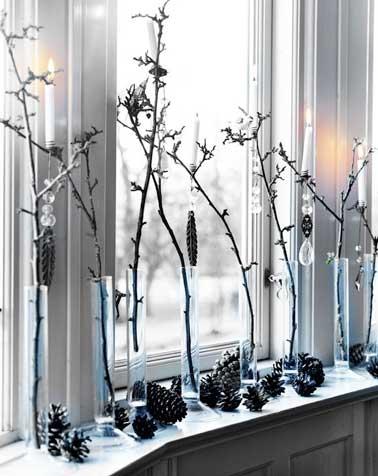 A Noël, les fenêtres se parent d'une déco noir et blanc à fabriquer avec des soliflores et des pommes de pins. Les décorations en verre transparent renforcent l'aspect givré.