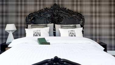 Une tête de lit en bois repeint en peinture de couleur noir dans une chambre pour une déco originale. Bonne idée pour moderniser le style d'une chambre traditionnelle