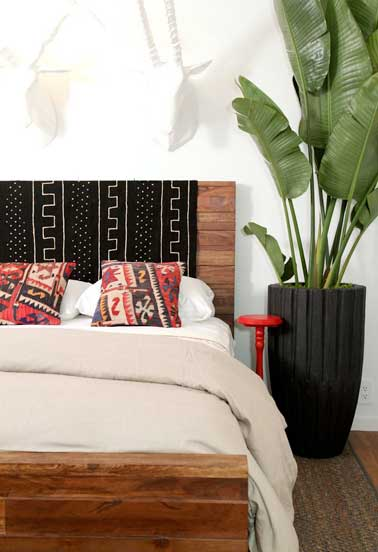 Originale cette tête de lit réalisée en palette de bois avec du tissu artisanal noir et blanc et coussins rouges. Pour une déco exotique dans la chambre.