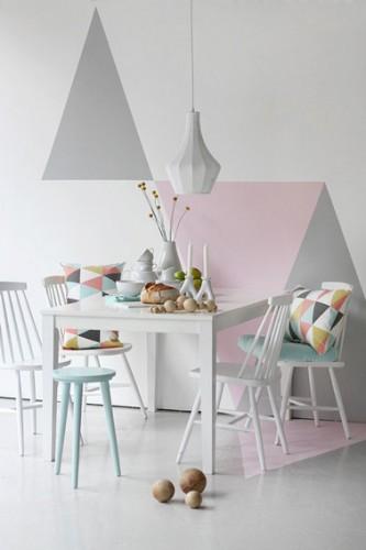 Une déco pastel qui joue avec les formes : Des triangles roses et gris de couleur pastel superposés sur les murs de la salle à manger pour une atmosphère douce et délicate.