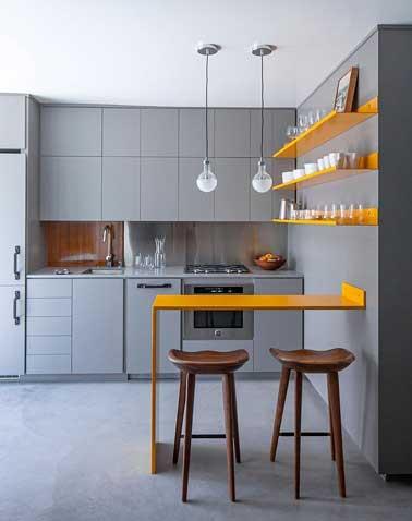 Avec le gris, la petite cuisine prend de la profondeur. La couleur orange brillante des étagères et du coin table rythme la déco et ajoute du tonus à la pièce