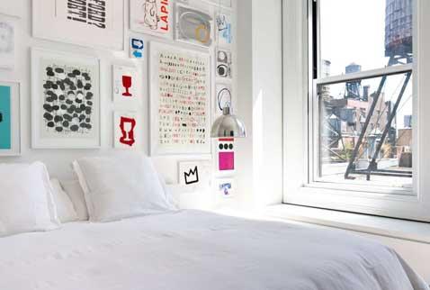 Des cadres photos assortis dans toutes les tailles fabriquent cette tête de lit. Une déco tout en couleur bienvenue dans une chambre blanche comme celle ci