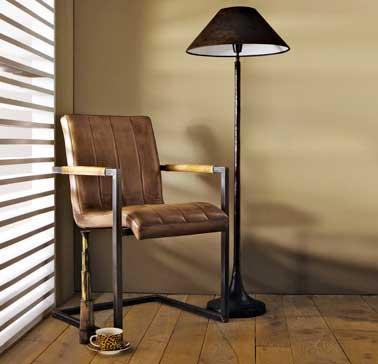 Une couleur kaki posée sur les murs du salon ajoute de l'exotisme à la pièce. Un ton puissant en accord avec le parquet et la chaise en cuir camel.Peinture Tollens