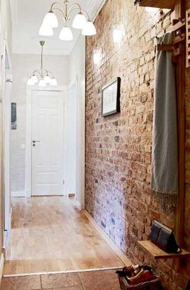Dans le couloir un mur de brique rouge installe une ambiance industrielle et structure l'espace étroit. Peinture blanche et luminaires ajoutent de la lumière