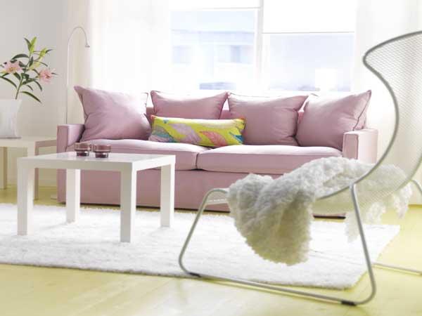 Un canapé en tissu rose quartz fait la déco du salon blanc. Parfait pour valoriser la table basse en bois blanc et le grand fauteuil design. Déco Ikea