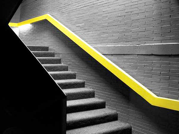 La cage d'escalier peinte en gris anthracite est bossée avec une rampe jaune fluo. Parfaite pour structure les lignes de l'escalier et lui donner de la lumière