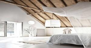 Une chambre sous combles voilà une bonne idée déco ! Chambre adulte ou d'amis aménagée sous combles profite des poutres et de la pente sous toit pour installer un cocon de rêve