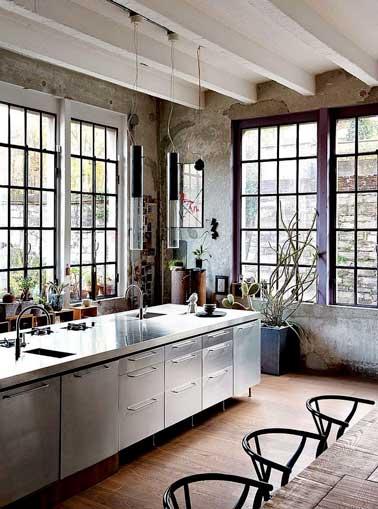 Beau mix de style avec le bois brut de la table et celui des verrières peint en violet. Déco contrastée par l'îlot central en acier et les luminaires design