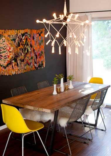 Chaises coques jaune pour animer la déco scandinave de cette pièce aux murs noirs. Une couleur claire et moderne assortie à la suspension lumineuse moderne