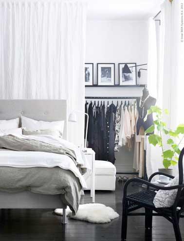 Un espace dressing est crée avec des rideaux blancs dans cette chambre parentale. Avec portant de vêtement et la lampe murale en acier noir comme déco loft