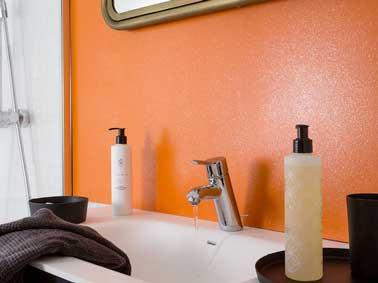 Une peinture orange pop réveille la salle de bain blanche. Ses effets pailletés, font une déco douce et vibrante à la fois pour dynamiser plan vasque et accessoires de bain