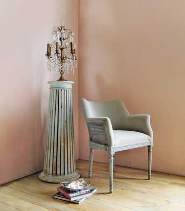 La couleur rose sur les murs et vert de gris pour le petit fauteuil et la colonne en bois repeint adoucissent cette pièce. Le lustre pampille ancien ajoute sa préciosité
