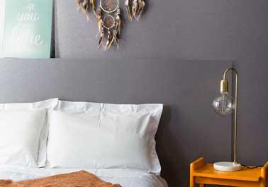 Tête de lit et mur s'entendent avec une couleur de peinture gris pailletté. Un mariage discret avec draps et oreillers blancs parfait pour valoriser la lampe design orange
