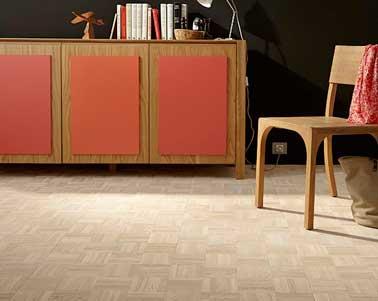 Un parquet massif en chêne est posé dans ce salon cosy. Il crée une douce harmonie de couleurs avec les meubles repeints en tons orange et la chaise en bois.