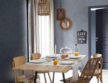 Douce harmonie dans la salle à manger peinte en gris pailleté. Mixée avec les tons chauds du bois présent sur la table, les chaises et les luminaires et miroir en osier