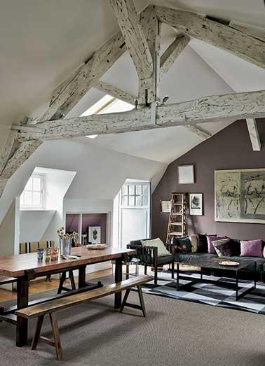 Dans la séjour sous pente une peinture aubergine sur un mur délimite l'espace salon. Déco décalée avec coussins assortis et échelle de bibliothèque chinés