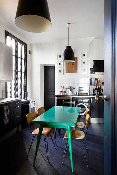 Une table de cuisine repeinte en vert c'est la touche funky de la déco de cuisine. Associée à une peinture noir satin pour repeindre les meubles de cuisine, le parquet et les portes de cuisine