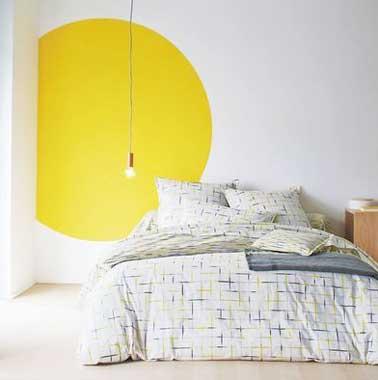 Un rond de peinture jaune punchy anime la déco de cette chambre blanche épurée. Dessiner une forme graphique est une idée à reprendre pour réveiller une pièce monochrome
