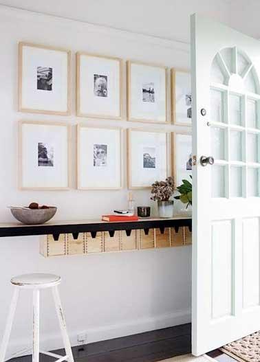 Accrochés contre le mur sur deux niveaux les cadres photos en bois clair habillent l'entrée avec élégance. Une déco simple et graphique pour les petits espaces
