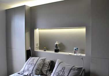 Tête de lit faite en coffrage bois entre deux placards dans une chambre grise. Avec ses led intégrés cette console pratique créée une ambiance cosy dans la pièce.