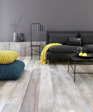 Plaid et coussins jaunes dynamisent le canapé noir et les tons sombres du salon gris. Placées en touche de couleur ils réveillent le camaïeux gris de la pièce