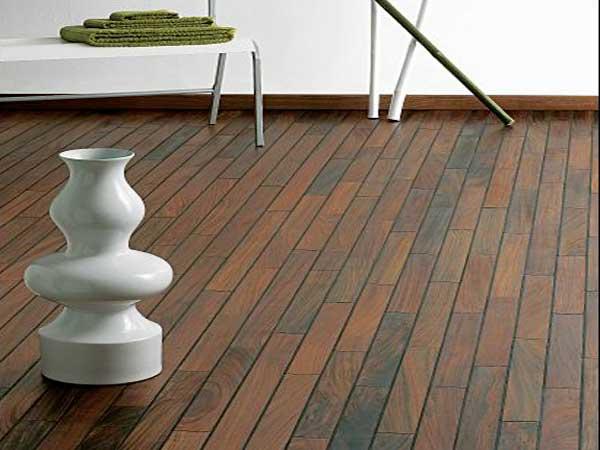 Déco moderne avec un parquet de salle de bain en mutenye. Ses nuances marron foncé sont parfaites avec une baignoire îlot et des meubles design