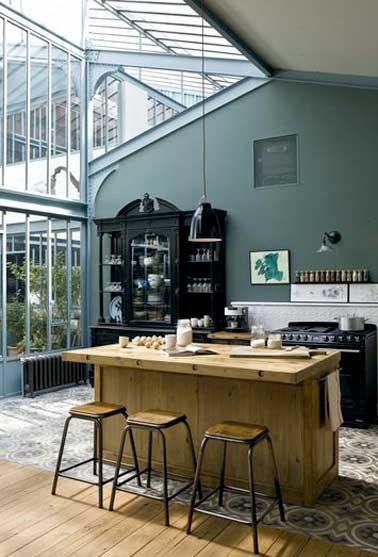 Une cuisine lumineuse avec sa verrière toit véranda. Espace structuré avec un sol en carreaux de ciment et déco loft pour l'îlot central et ses tabourets en bois