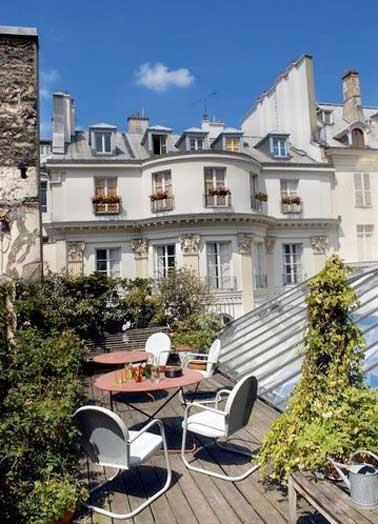 Un salon d'extérieur au charme urbain et cosy réalisé avec deux tables de jardin en fer et des chaises blanches design. Abrité du vis à vis par une végétation fournie il gagne en intimité