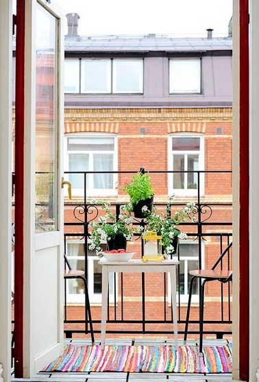 Adopter un accessoire de couleur sur son balcon est une bonne astuce pour moduler sa déco sans refaire tout l'agencement d'extérieur. Ici un tapis de sol multicolore est placé sur la terrasse