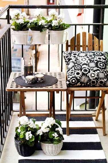 Un angle de balcon au carré avec table de jardin et chaise en bois alignés contre la balustrade. En symétrie, jardinières suspendus, paniers en osiers et tapis de sol à rayures noirs et blancs