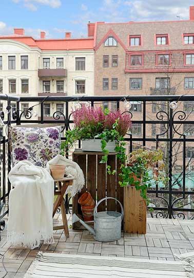 Sur le balcon, un coin jardin suspendu est aménagé sur des vieilles caisses récup. Une chaise pliante en bois et un arrosoir en acier galvanisé signent une déco romantique