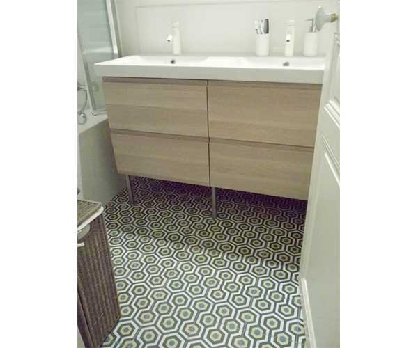 Carreaux de ciment géométriques verts et blancs dans petite salle de bain contemporaine. Modernisé par le meuble sous lavabo double vasque en bois clair et les murs blancs de la pièce.