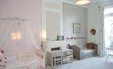 Pour délimiter le côté fille et le côté garçon, le papier peint à pois effectue une transition en douceur de la chambre de princesse rose à l'espace garçon gris souris.