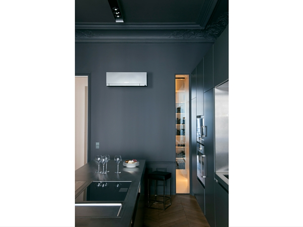 Ici, on a peint tous les murs dans un gris foncé en camaïeu avec les portes des meubles de cuisine. La climatisation gris clair vient se détacher sur le mur.
