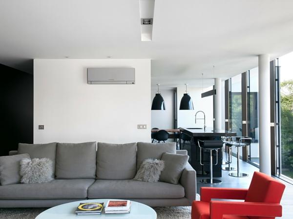 Ce climatiseur gris est en accord parfait avec le canapé du salon et assure chaleur en hiver et fraîcheur en été. Le fauteuil rouge tranche et romp la sobriété du gris.