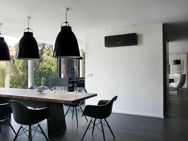 Ce climatiseur Mitsubishi noir est fixé en hauteur sur un mur blanc pour maintenir une température constante dans la salle à manger. On ne le remarque presque pas !