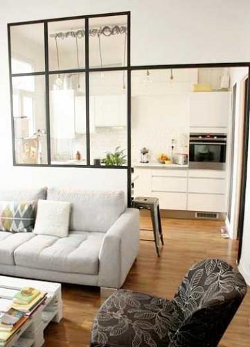 Déco de cuisine arty autour d'une cloison verrière en acier valorisée par une suspension linéaire. Crédence en carrelage métro et meubles de cuisine blancs coordonnés.